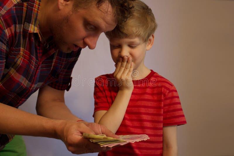 L'homme et le garçon tiennent l'argent dans leurs mains photo stock