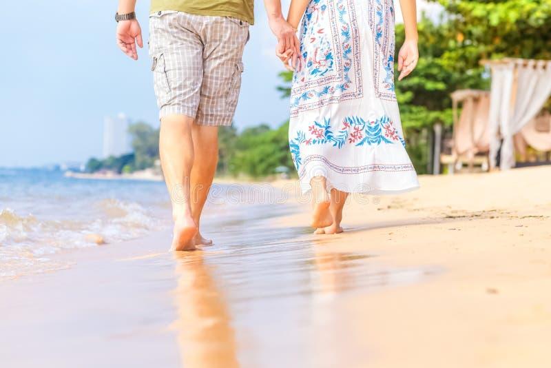 L'homme et les femmes tiennent sa main sur la plage et l'avant du coucher du soleil ils sont des couples ils marchent sur le sabl images stock