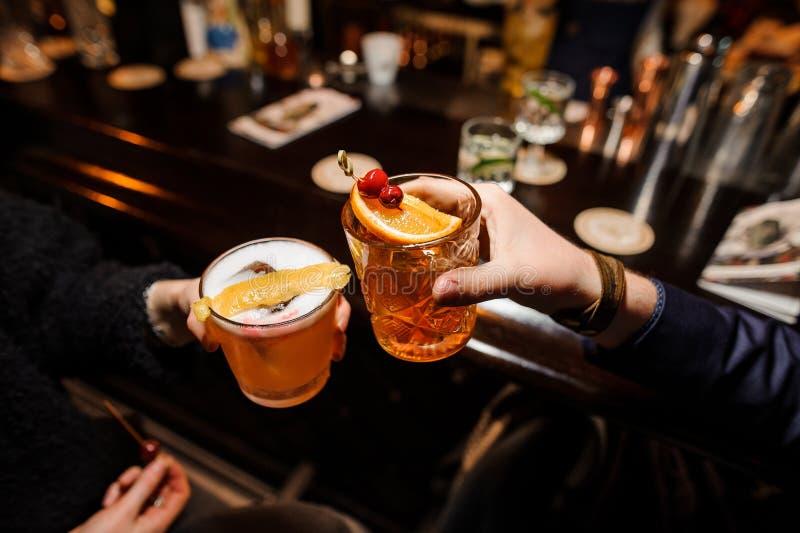 L'homme et une femme s'asseyent à un compteur de barre et à des verres tintants de cocktails alcooliques image stock