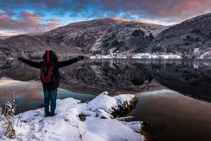 L'homme excité par la beauté du lac et les montagnes aménagent en parc en hiver au crépuscule image stock
