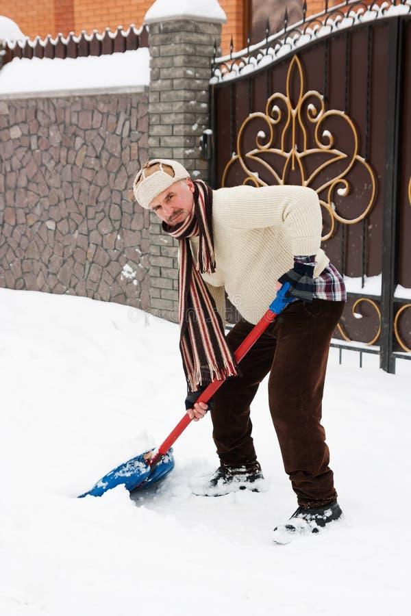 L'homme fâché dégage la neige images libres de droits