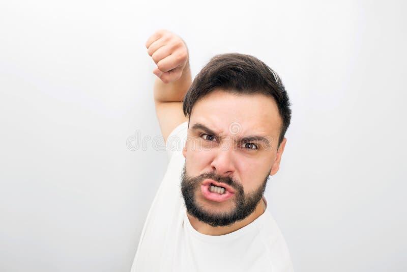 L'homme fâché même regarde sur la caméra Il est prêt à combattre avec le poing qu'il pose D'isolement sur le fond blanc image stock