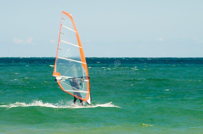 L'homme faisant de la planche à voile est porté sur la mer bleue dans la perspective d'un beau ciel photos libres de droits