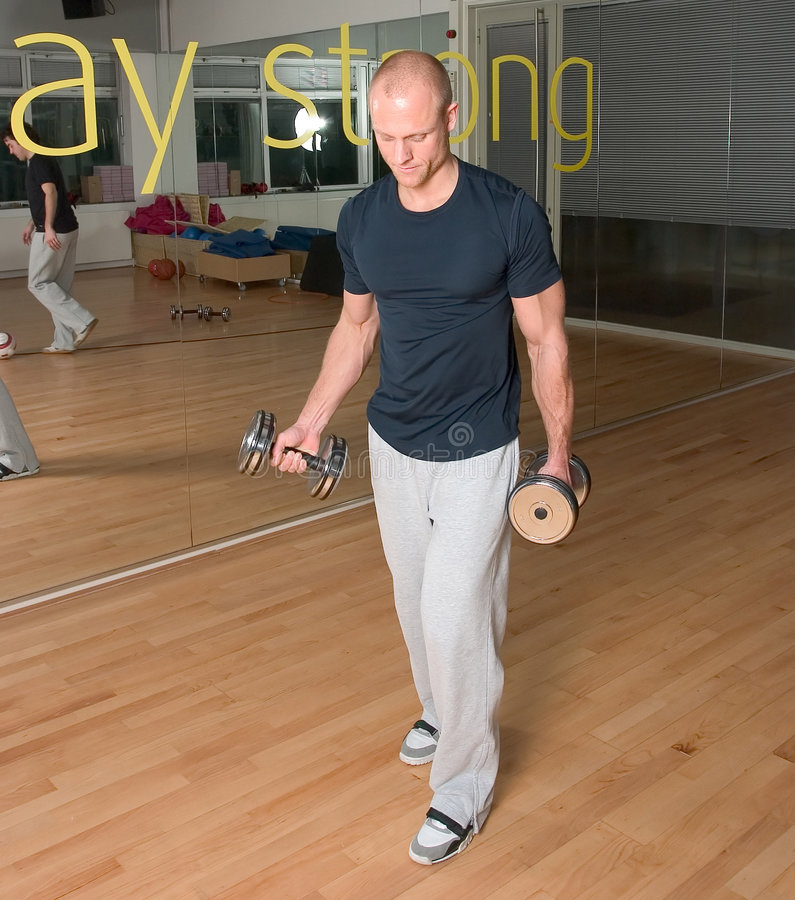 L'homme faisant le biceps s'enroule en gymnastique photo stock