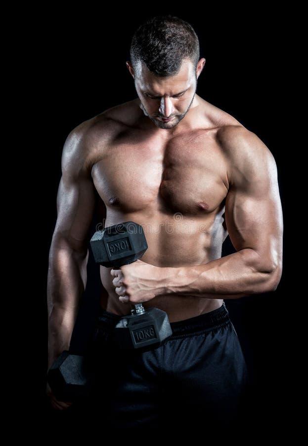 L'homme faisant le biceps se courbe dans le gymnase photo libre de droits