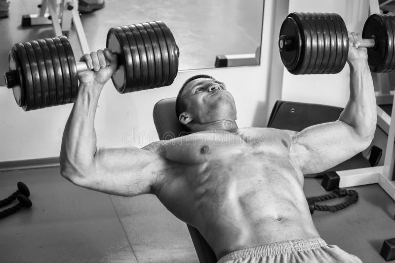 L'homme fait des haltères d'exercices photos stock
