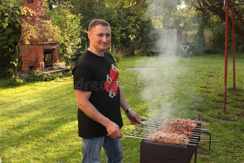 L'homme fait frire le rassemblement dans le jardin Nourriture sur la brochette, gril, barbecue photo stock