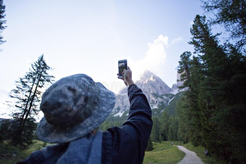 L'homme fait la photo des montagnes et de la forêt photos libres de droits