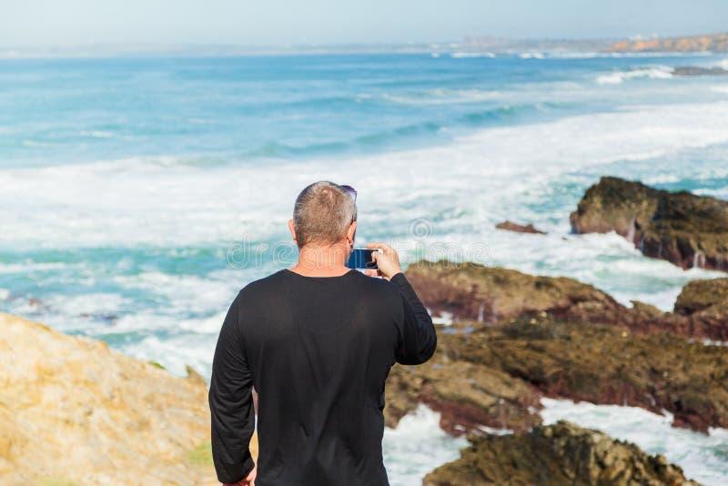 L'homme fait la photo du paysage marin images libres de droits