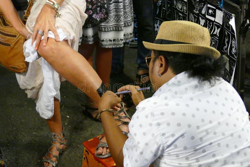L'homme fait le tatouage d'aérographe sur la jambe de touristes au marke de nuit images stock