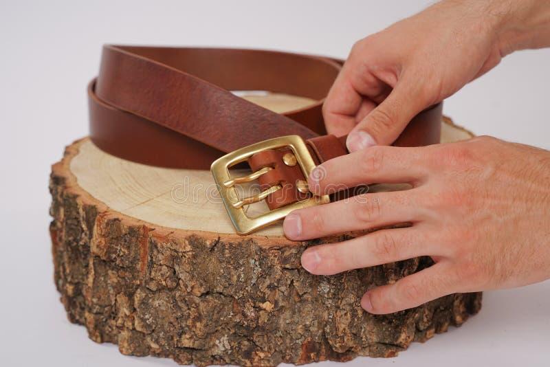 L'homme fait par la ceinture en cuir de mains avec la boucle Passe-temps fait main jeune homme reposant par fabrication ses ceint photographie stock libre de droits