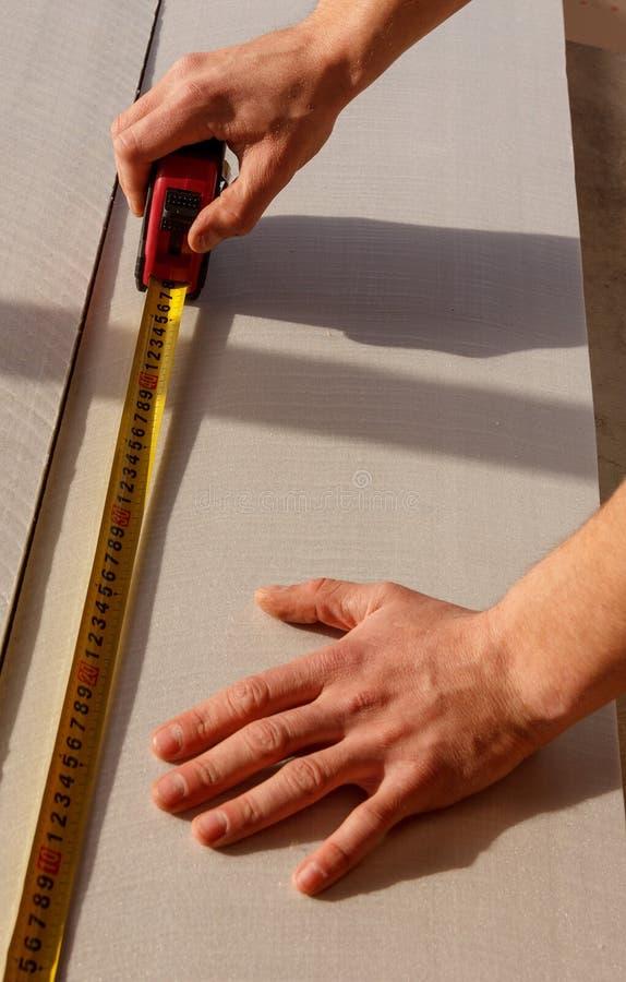 L'homme fait une inscription avec le ruban métrique sur une feuille de matériel sain de preuve images libres de droits