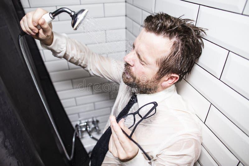 L'homme fatigué dans une chemise et un lien a fermé ses yeux et s'est penché contre le mur dans la salle de bains, tenant des ver photos stock
