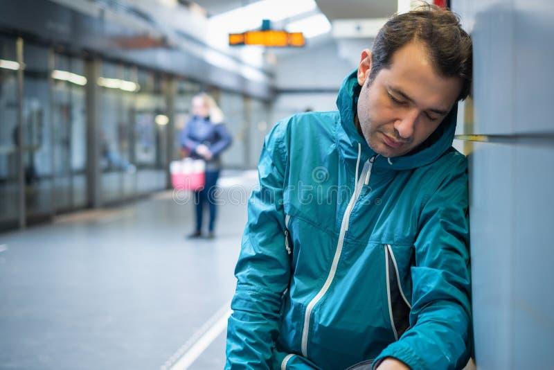 L'homme fatigué dort dans la station de train de métro images stock