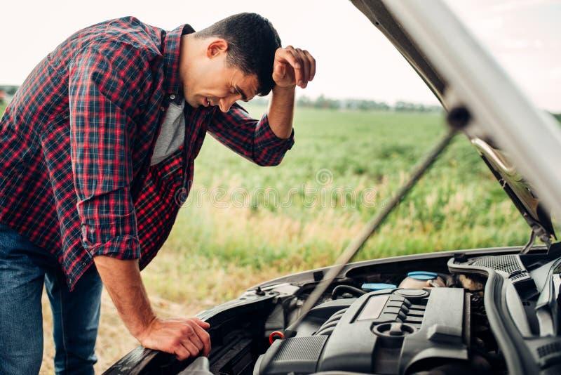 L'homme fatigué essaye de réparer une voiture cassée images stock