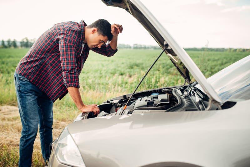 L'homme fatigué essaye de réparer une voiture cassée photo libre de droits