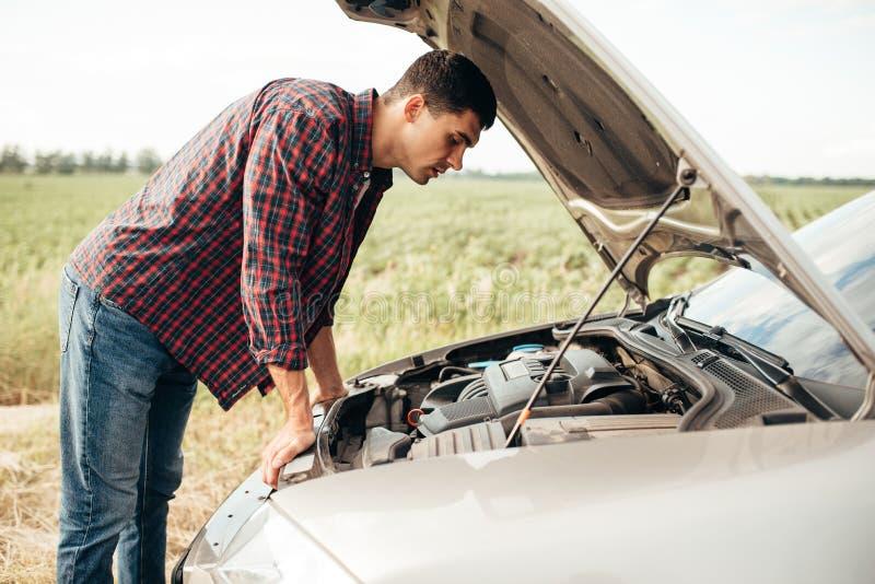 L'homme fatigué essaye de réparer une voiture cassée image libre de droits