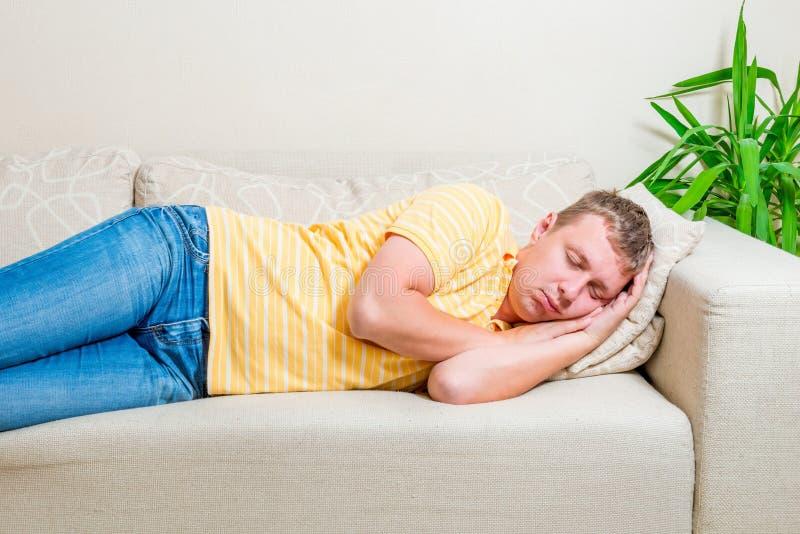 L'homme fatigué fixent pour prendre un petit somme sur le sofa photo stock