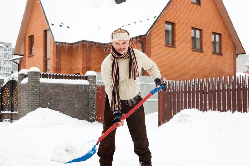 L'homme fatigué nettoie la neige photos libres de droits