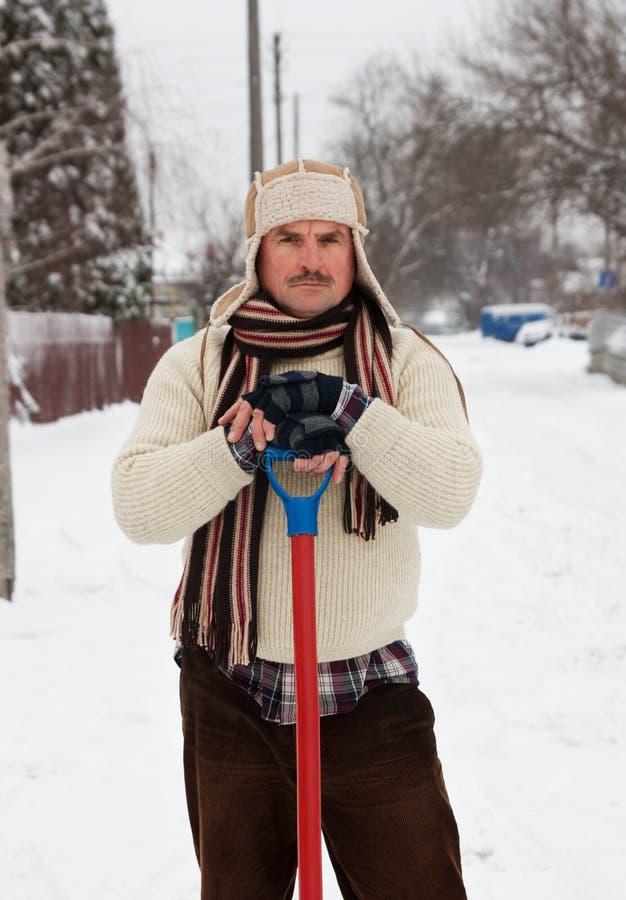 L'homme fatigué nettoie la neige image libre de droits