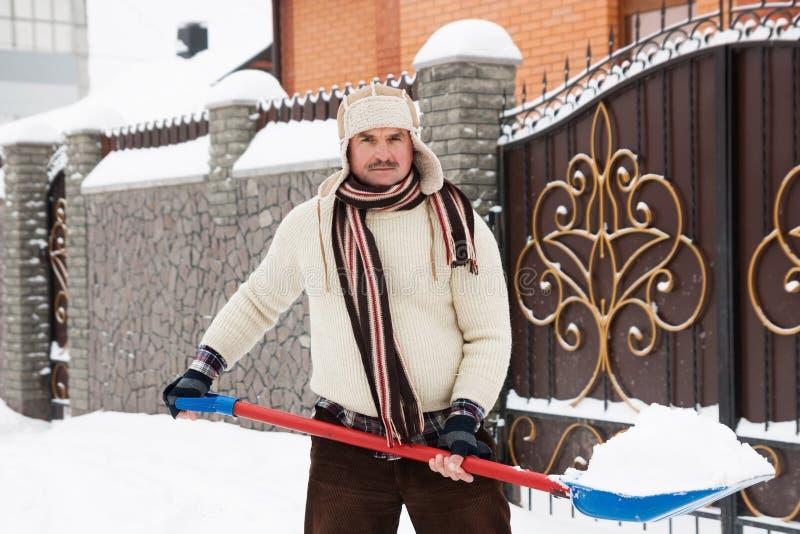 L'homme fatigué nettoie la neige images stock