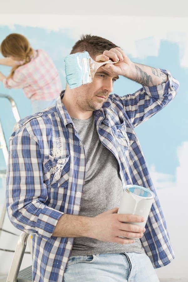 L'homme fatigué tenant la peinture peut et brosse avec la peinture de femme à l'arrière-plan photo libre de droits