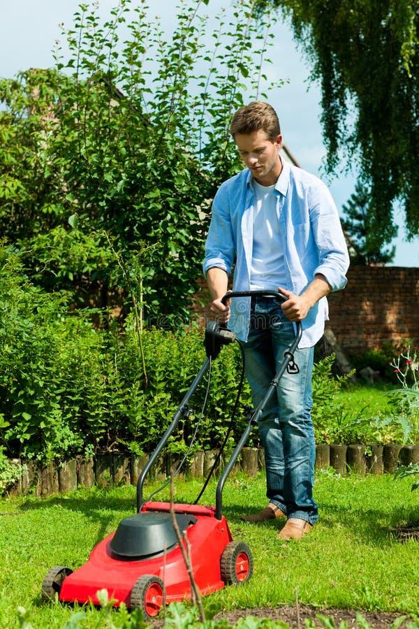 L'homme fauche la pelouse en été photo libre de droits