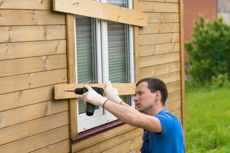 L'homme ferme les fenêtres de la maison avec des conseils, vue de côté images stock