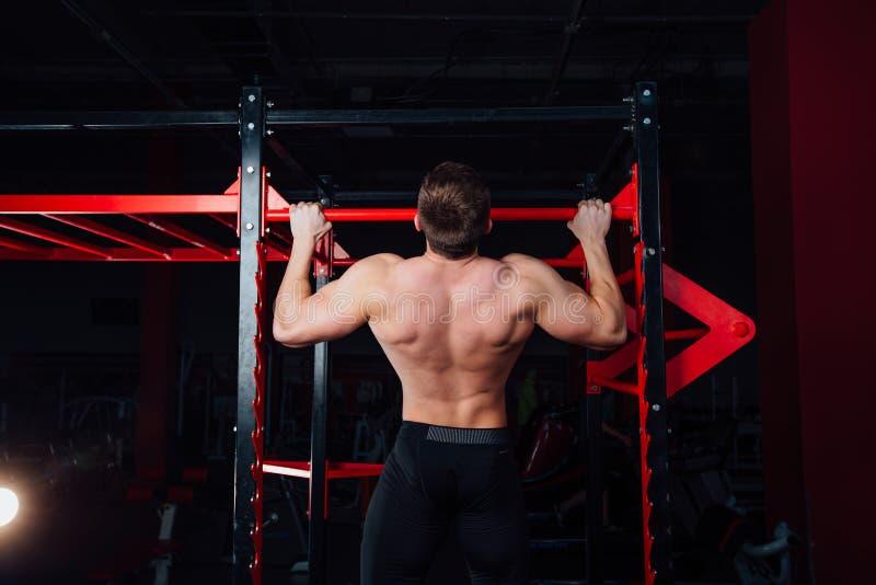 L'homme fort faisant la traction lève l'athlète bel au gymnase grande formation musculaire sûre images stock