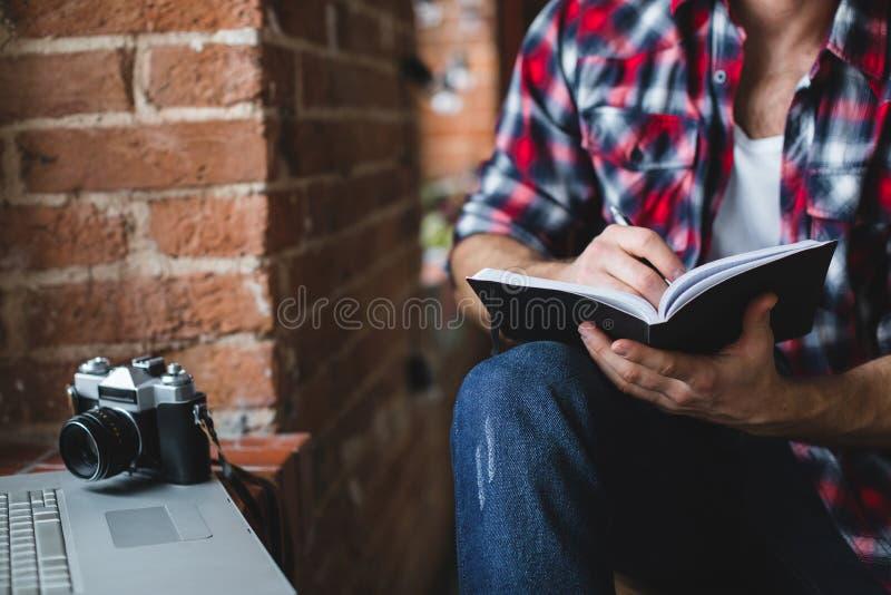 L'homme gai avec un ordinateur portable écrit dans un plan rapproché de carnet images stock