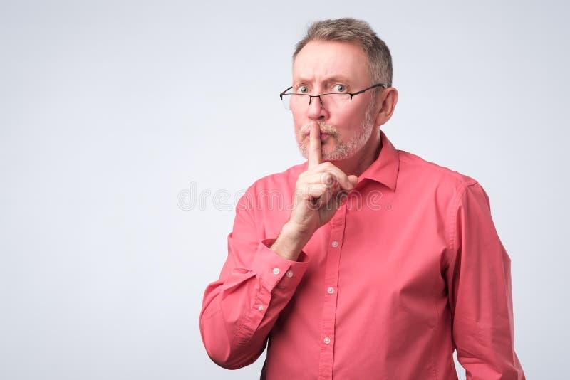 L'homme garde le doigt sur des lèvres, essais pour maintenir secret images stock