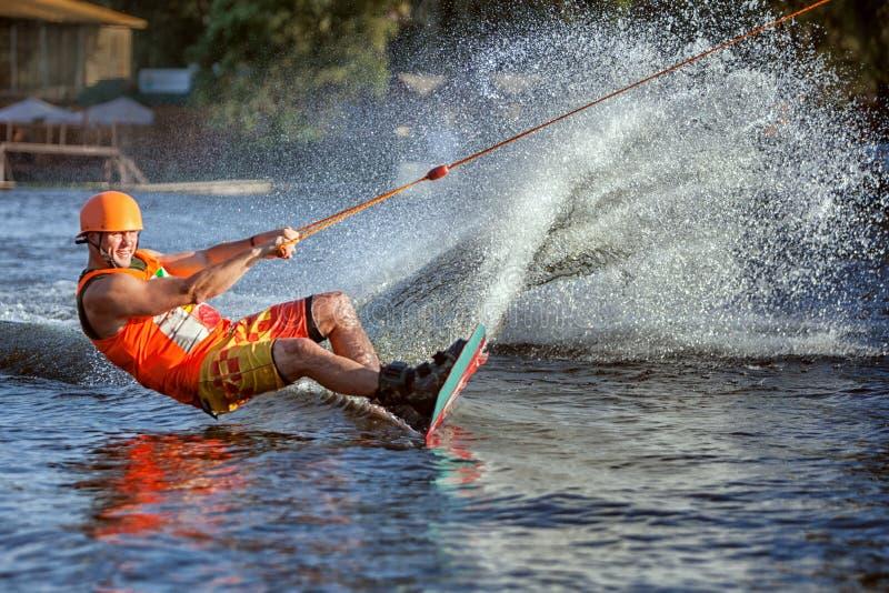 L'homme glisse sur le conseil sur l'eau photos stock