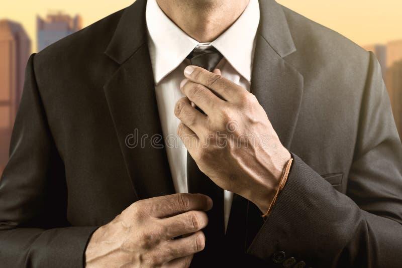 L'homme habillé dans le costume et la chemise blanche ajuste son lien photographie stock libre de droits