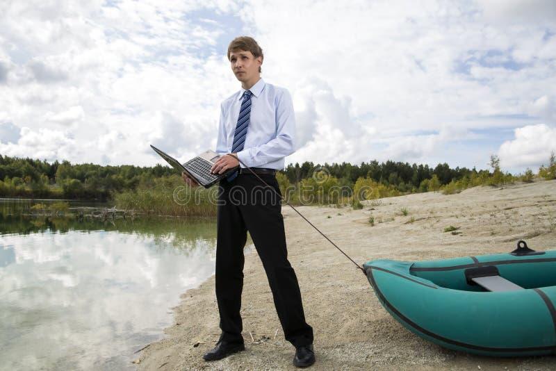 L'homme habillé traîne le bateau au-dessus du rivage de lac photos stock