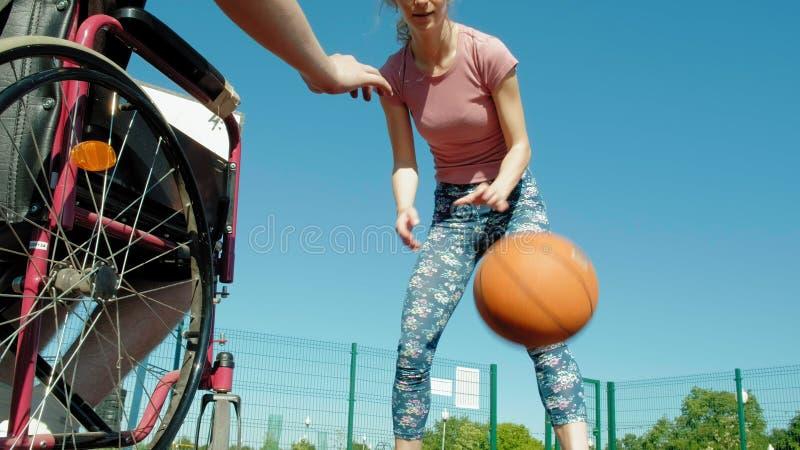 L'homme handicapé joue au basket-ball de son fauteuil roulant avec une femme, sur l'air ouvert, font un effort en jouant photos libres de droits