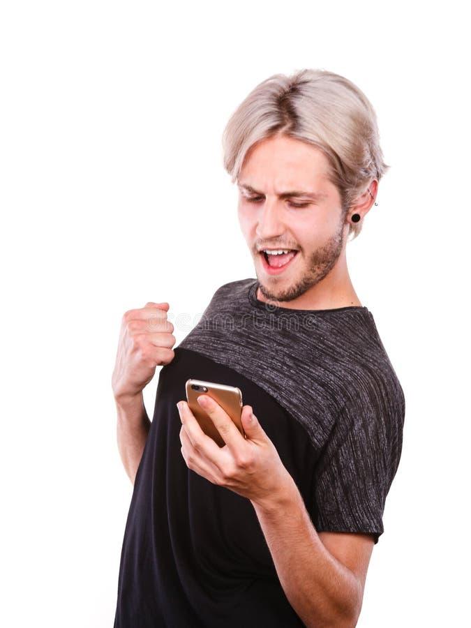 L'homme heureux à l'aide du téléphone portable a lu le message photographie stock