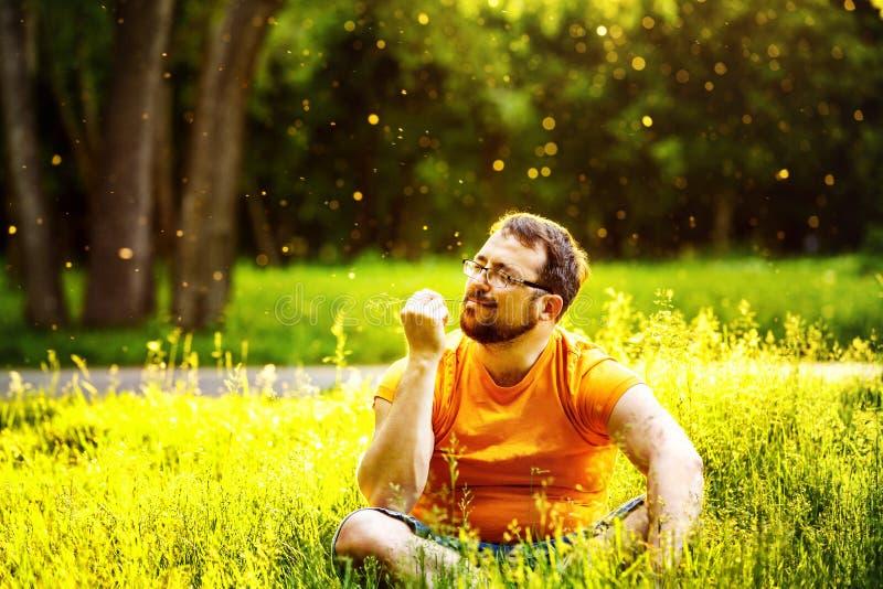 L'homme heureux amical s'assied avec les yeux fermés en parc vert photos stock