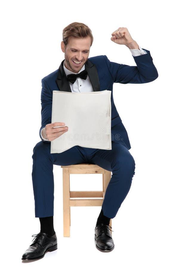 L'homme heureux assis célèbre la victoire tout en lisant de bonnes nouvelles image stock