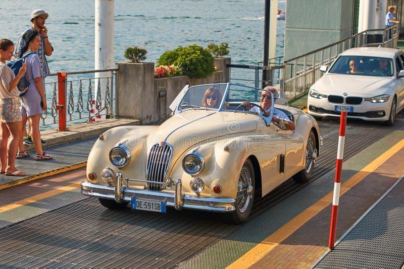 L'homme heureux chasse son vintage Jaguar beige XK120, une voiture de sport construite par Jaguar vers 1950, du ferry-boat photo libre de droits