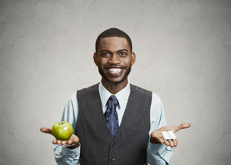 L'homme heureux d'affaires tient la pomme et les pilules vertes images libres de droits