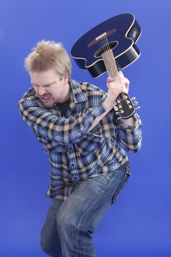 L'homme heurte sa guitare sur l'étage photos libres de droits