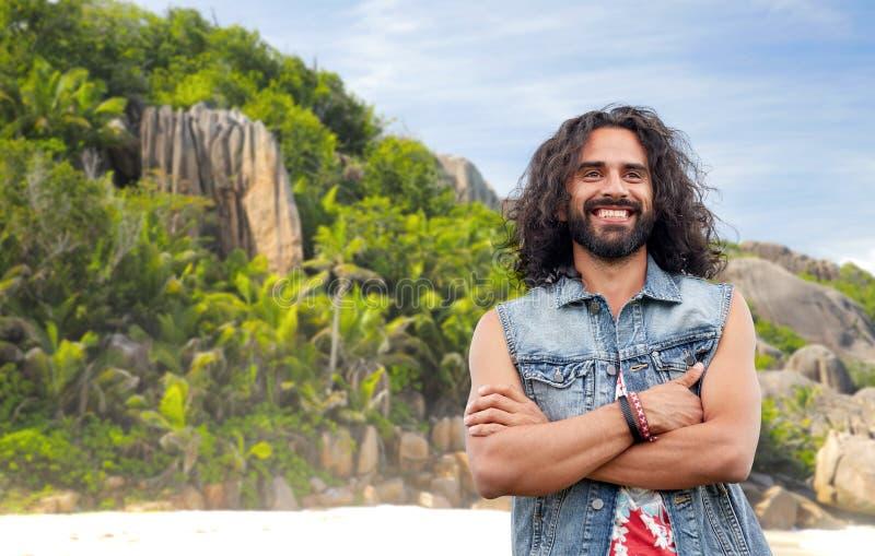 L'homme hippie de sourire en denim investissent sur la plage d'île images libres de droits