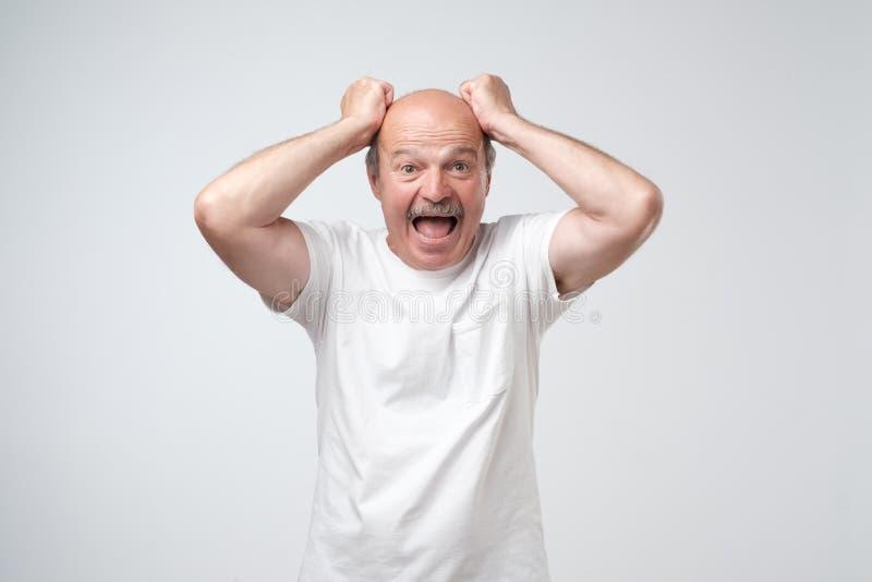 L'homme hispanique mûr sent le choc et la surprise avec excessivement faire face à l'expression images stock