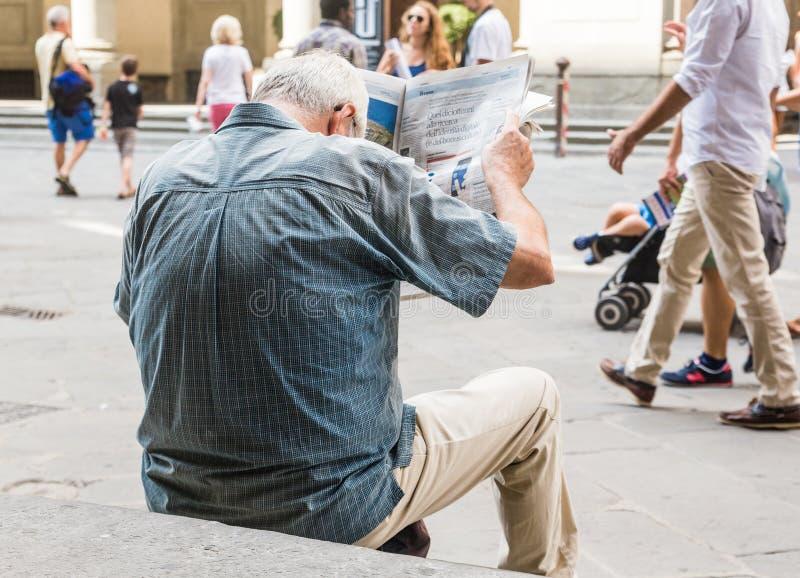 L'homme inconnu lit le journal sur Piazzale Degli Uffizi photographie stock libre de droits