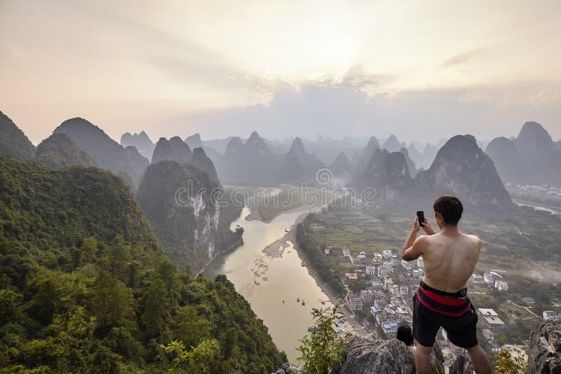 L'homme inconnu prend la photo avec un téléphone portable de vue de Li River au coucher du soleil photos libres de droits