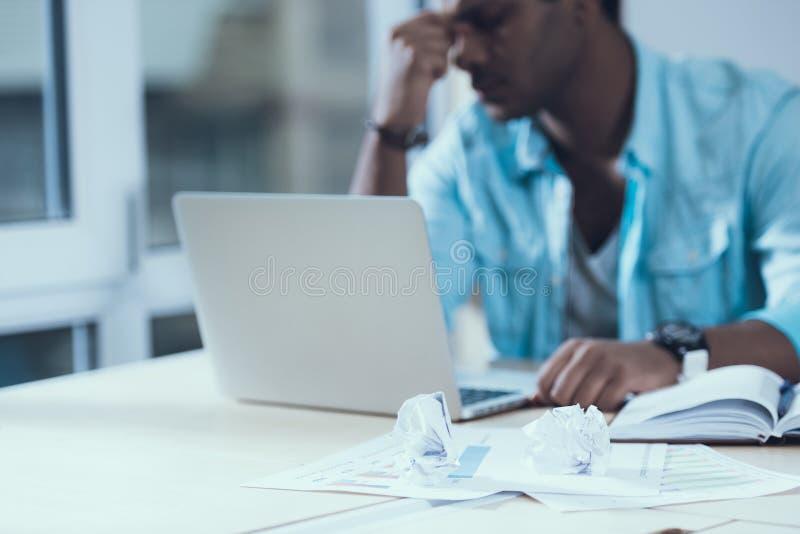 L'homme indien fatigué s'assied derrière l'ordinateur portable dans le bureau Crise idéologique Feuilles chiffonnées images stock