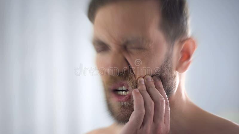 L'homme inquiétant de mal de dents pointu, carie dentaire, gingivite, a brouillé l'effet images libres de droits