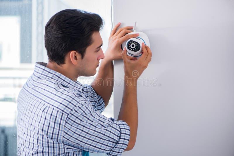 L'homme installant des appareils-photo de télévision en circuit fermé de surveillance à la maison images stock