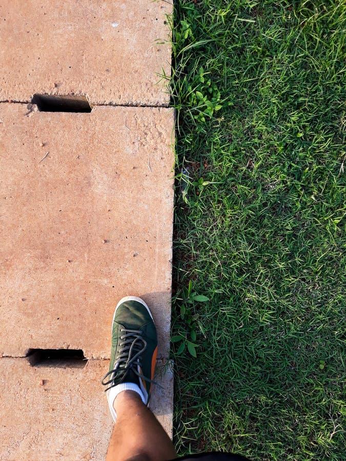 L'homme intensifient sur le pied droit dans l'espadrille verte grille de drain de ciment et herbe verte avec le fond abstrait photos libres de droits