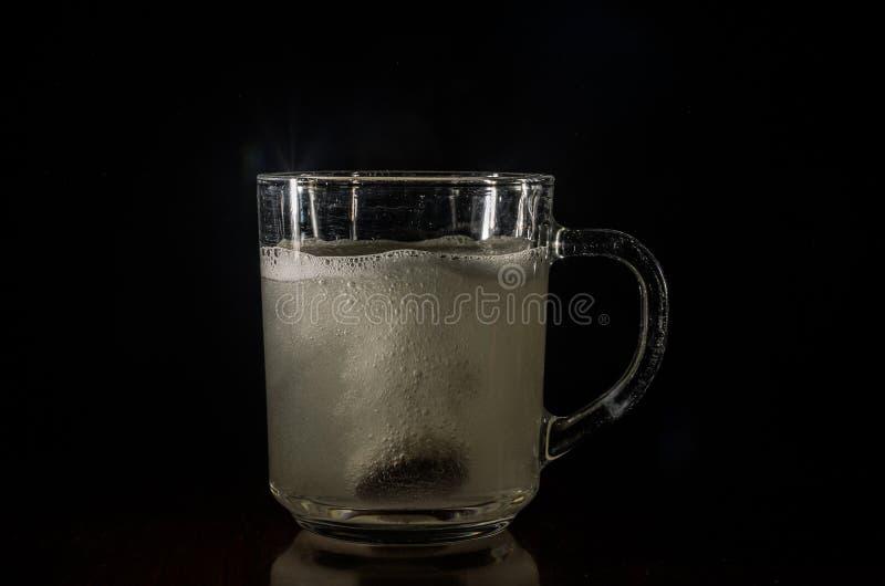 L'homme jette le comprimé effervescent dans l'eau photographie stock libre de droits